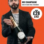 Advertising commercial portrait photography session featuring young man with beard holding bottle of wine and making funny face.