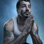 Creative portrait of a man with tattoos sitting and preying by London portrait photographer Nikolay Mirchev.