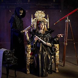 four handed Queen seating on a throne receiving scripts from her Demon servant, and pointing at a Victorian style globe