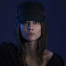 young and pretty female model wearing black hat is posing for creative fashion photoshoot, photographed in a deemed blue background.
