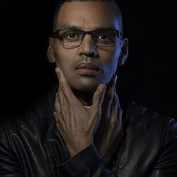 Headshots London Low key portrait of a black man wearing glasses and a black leather jacket, having his hands and fingers very close to his face