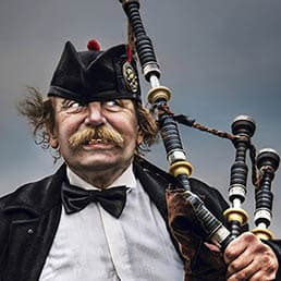 Scotsman with big moustache performing music with his bagpipe at Westminster Bridge in London
