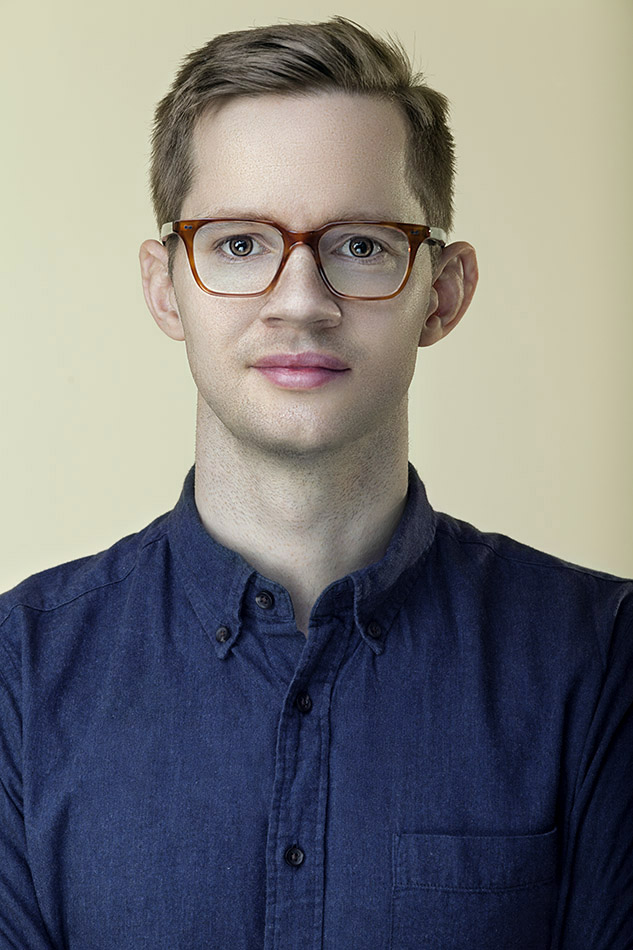 Corporate Headshot portrait of a young man wearing glasses and blue shirt, photographed on cream colored background.