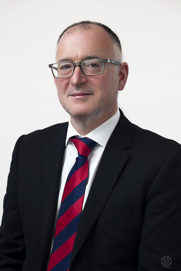 Corporate headshot of a man with glasses on location