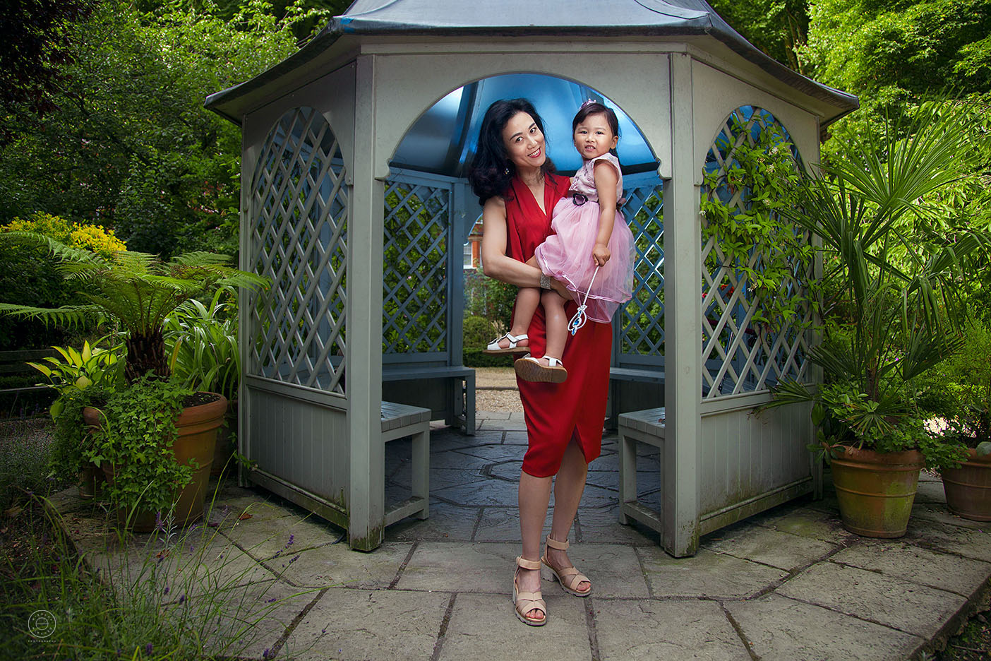 Family portrait session in South West London - mum holds her little daughter in her arms for a picture.