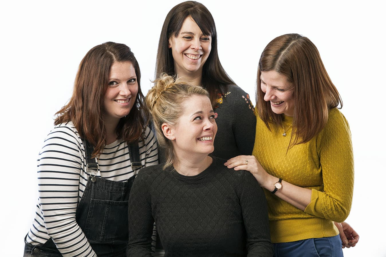 Four sisters laughing as they pose for family portrait in a studio with a white background