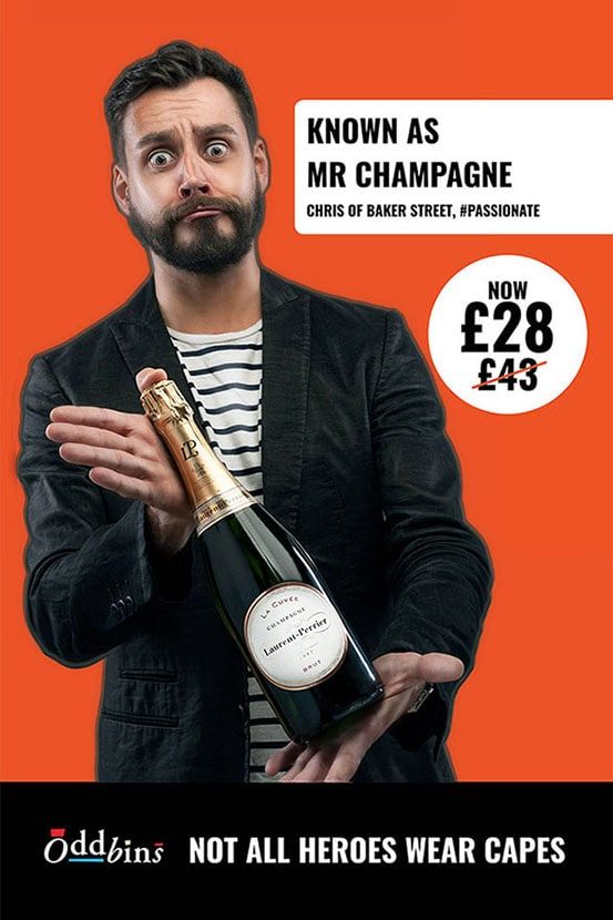 Commercial portrait featuring a shop worker as a model holding a bottle of newly introduced range of Champaign