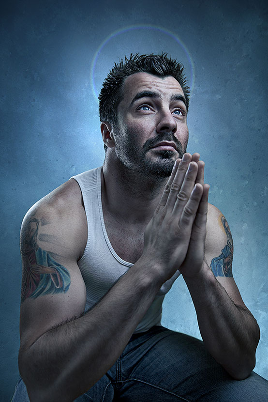 Creative portrait of young man covered with religious tattoos sitting and praying