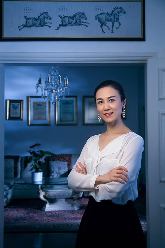 A chines business woman photographed on the backdrop of her apartment in London